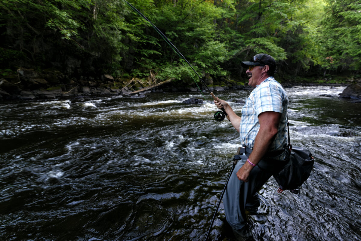 An angler smiles as a bass runs downstream.