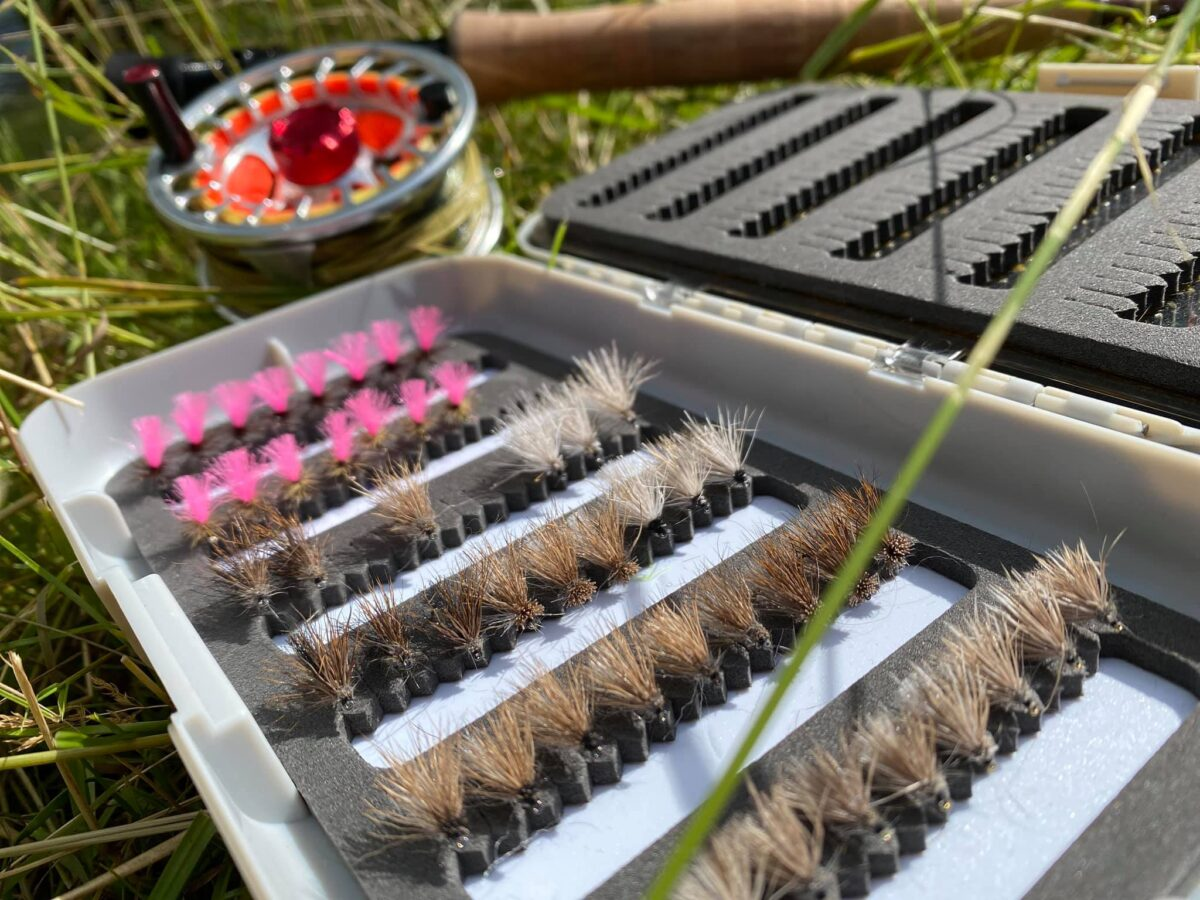 A full box of dry flies with a reel in the background.